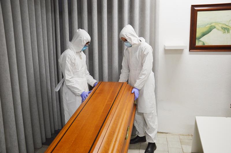 Os profissionais usam máscaras, luvas e batas no seu trabalho de recolha dos corpos